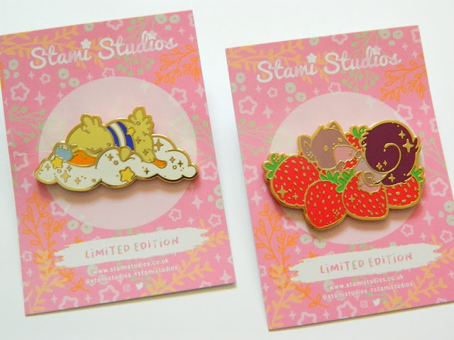 A photo showing two pin badges, one of a sleeping duck and the other of a squirrel eating strawberries