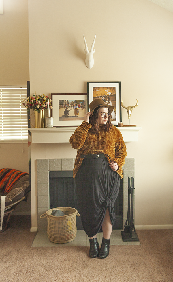 An outfit consisting of a brown floppy hat, a dark yellow chenile sweater tucked into a belt over a black maxi dress, tied in a knot at the knee with black heeled Chelsea boots.