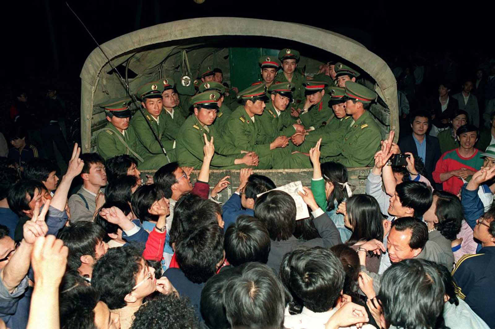 Pro-democracy demonstrators raise their fists and flash the victory sign in Beijing while stopping a military truck filled with soldiers on its way to Tiananmen Square on the day when then Prime Minister Li Peng declared Martial Law, May 20, 1989.