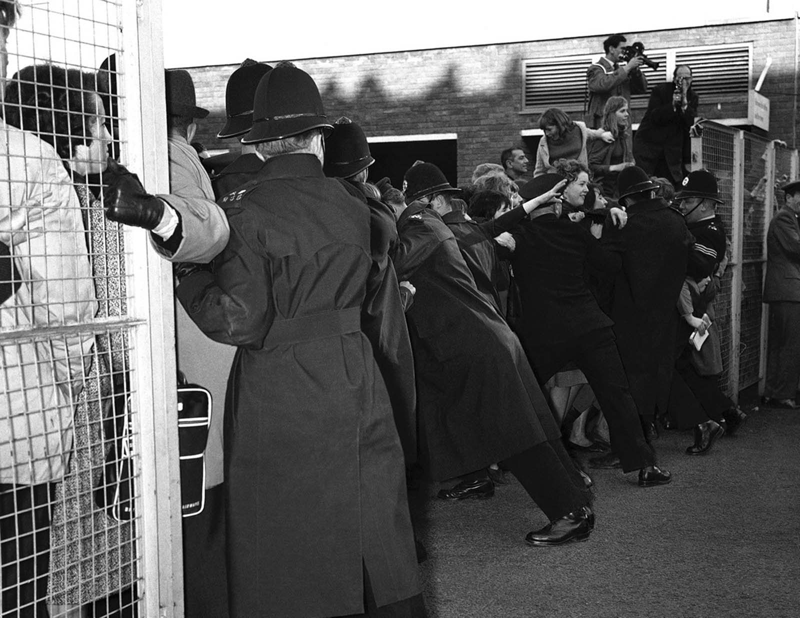 Police hold back screaming fans fighting to get near their idols, the Beatles, when the Liverpool pop group returned to London Airport from Paris, on February 5, 1964. A strong police escort had to accompany the four Beatles from their aircraft to the customs channel.