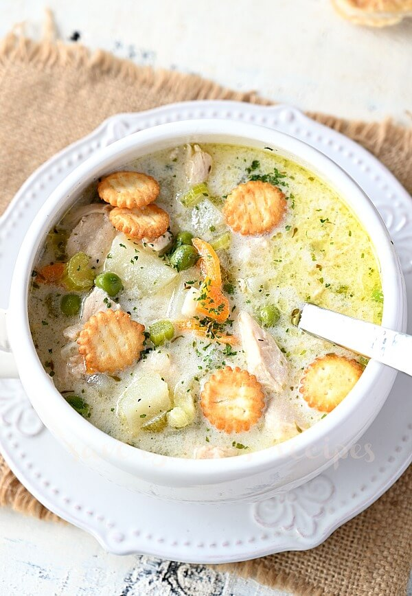 a white bowl with chicken pot pie soup topped with crackers