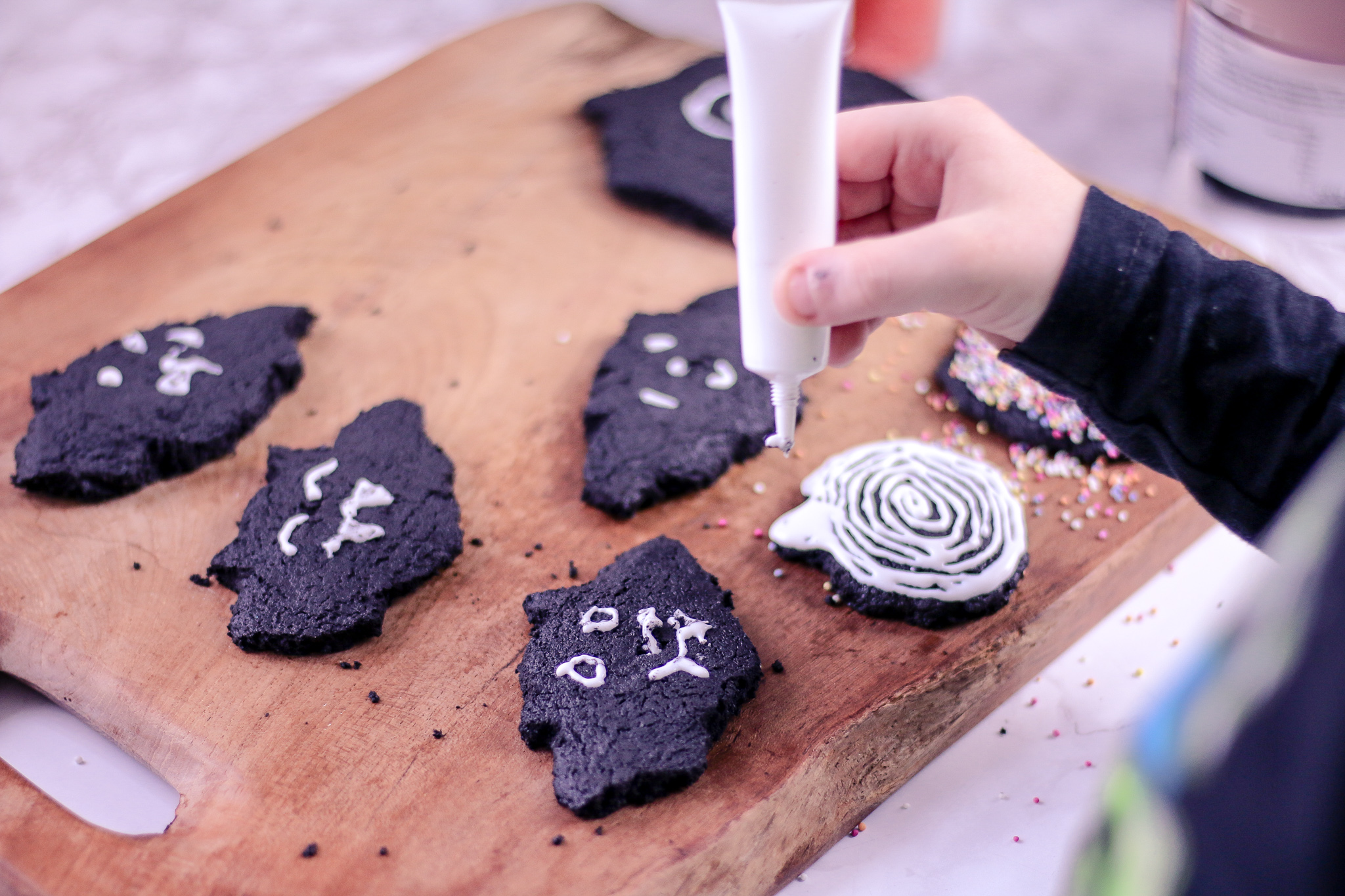 Close up photo of a child decorating biscuits with an icing pen