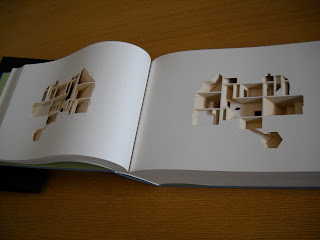 An open book. The pages are blanked have elements cut out to create the image of a house layout.