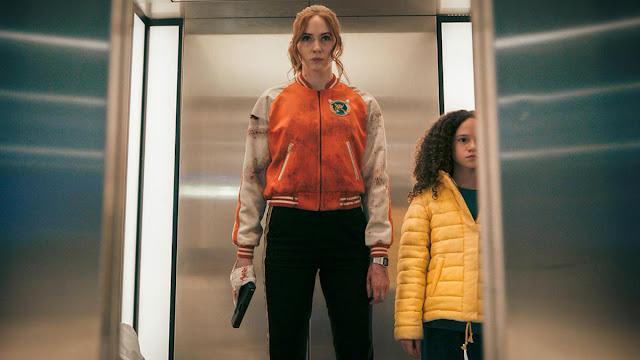 karen gillan with a gun and child in an elevator