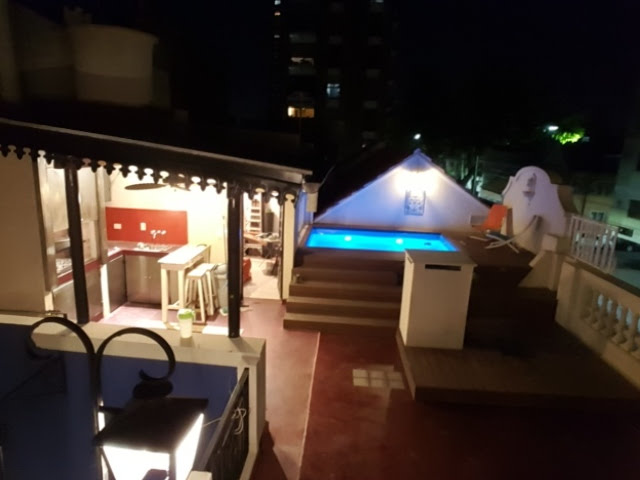 Roof terrace with pool and parrilla at night