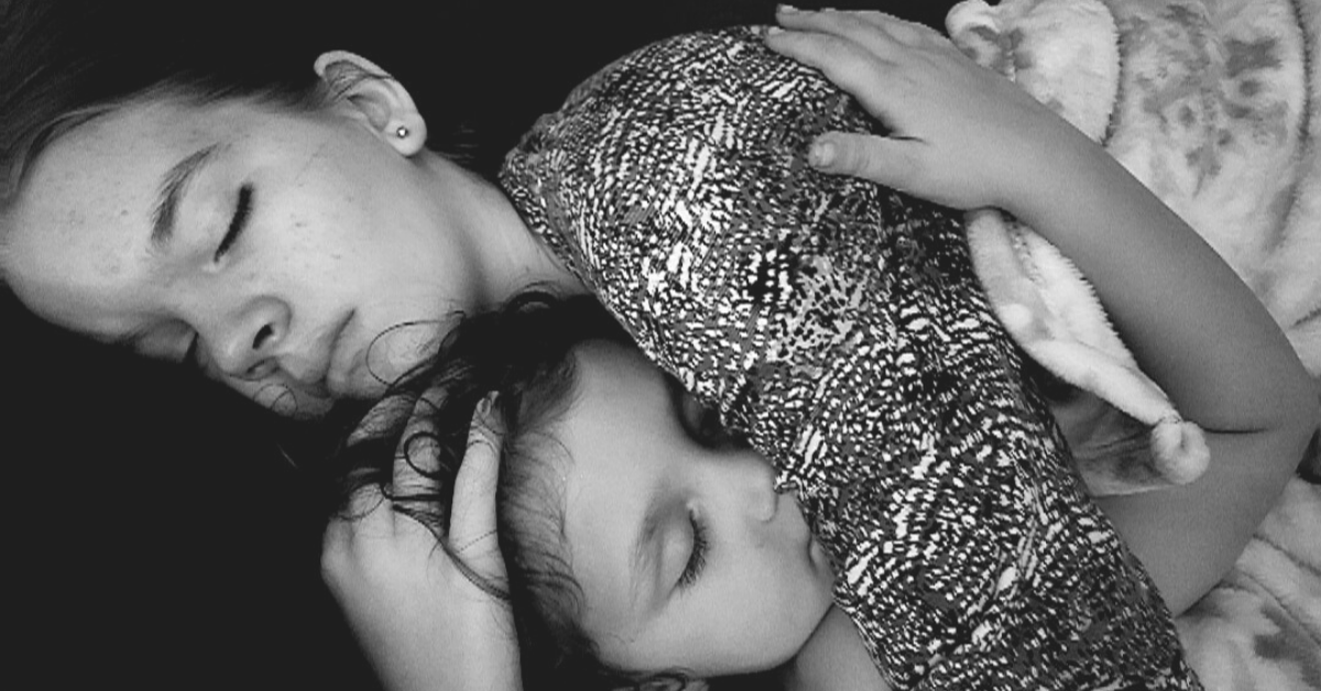 Two daughters cuddling with each other in a black a white photo.