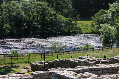 Photo showing the ruins of the bath house with the river behind, fast flowing over the stones.