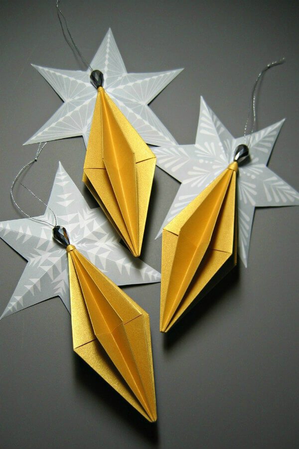 A trio of metallic gold paper Diamond Origami Ornaments resting on folded paper stars
