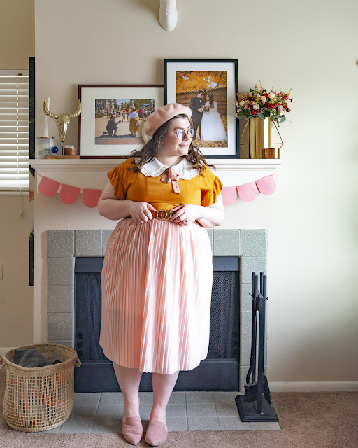 An outfit consisting of a pastel pink beret, a white oversized ruffle peter pan collar under a mustard yellow dress with flounce sleeves under a pastel pink pleated midi skirt and dusty pink pointed toe mules.