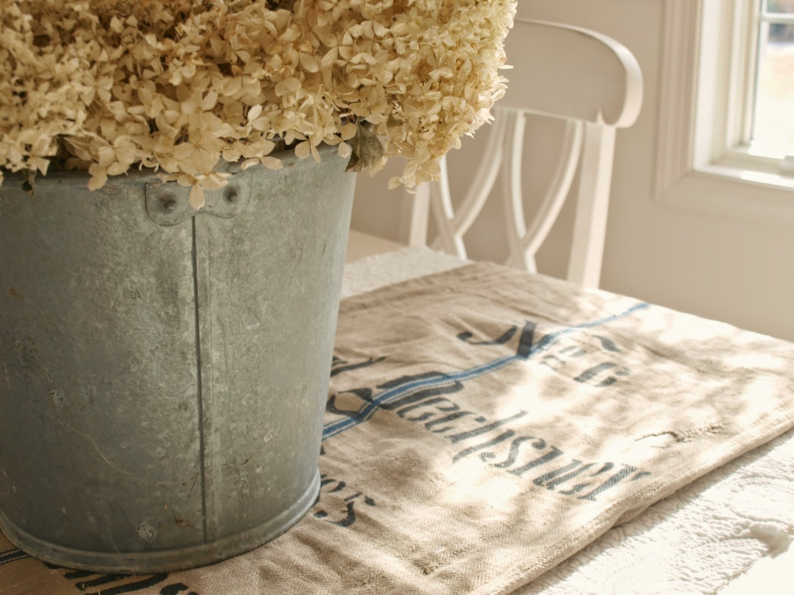 Antique grain sack as table runner in Nordic French dining room by Hello Lovely Studio. #grainsack #frenchcountry #frenchfarmhouse #galvanized #hydrange #diningroom