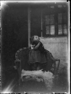 junges Mädchen mit Kuscheltier auf Stuhl - um 1910