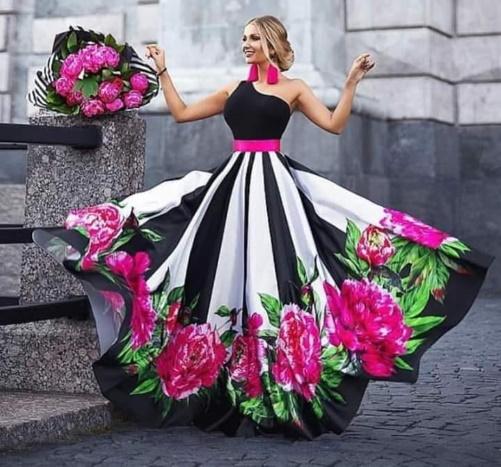 Linda jovem com um vestido floral, com ar de felicidade.