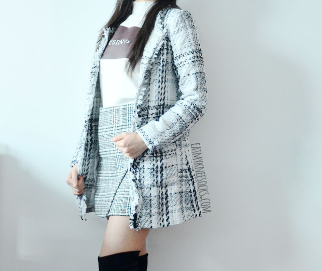 An elegant, chic monochrome outfit featuring a Chanel-inspired gridded tweed longline coat, asymmetric houndstooth sheath skirt, and printed mock-neck dip hem sweater from SheIn.