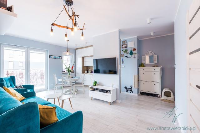 Salon z aneksem kuchennym w stylu skandynawskim, z oryginalnym rozwiązaniem ścianki multimedialnej.