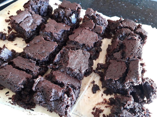 Image shows chocolate brownies which have just been cut into squares