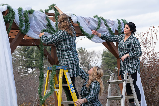 Getting Ceremony Area Ready Women putting veil and greenery on wooden arch outside Magnolia Farm Asheville Wedding Photography captured by Houghton Photography
