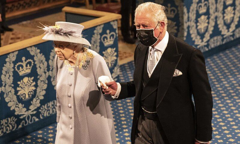 Queen Elizabeth wore a grey jacquard coat with lemon flowers, and a grey and yellow silk dress, and hat by Angela Kelly