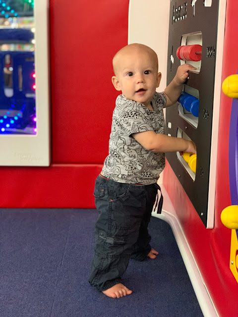 7 month old baby boy standing up while holding on to a play abacus