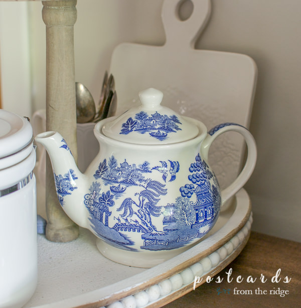 blue and white vintage teapot and thrifted items in a wooden tiered tray