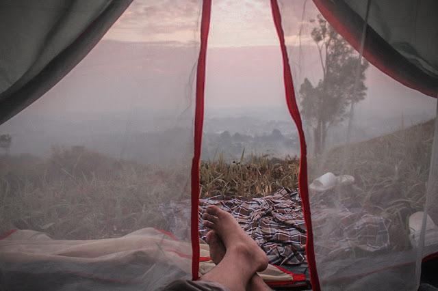 kaki saya di pintu tenda dengan pemandangan kota dari ketinggian yang diselimuti kabut bukit wangun atau taman ilalang cijeruk bogor