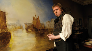 Still from the film Mr Turner - Timothy Spall as JMW Turner standing in front of a painting of ships