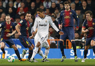 Raphael Varane surrounded by four Barcelona players