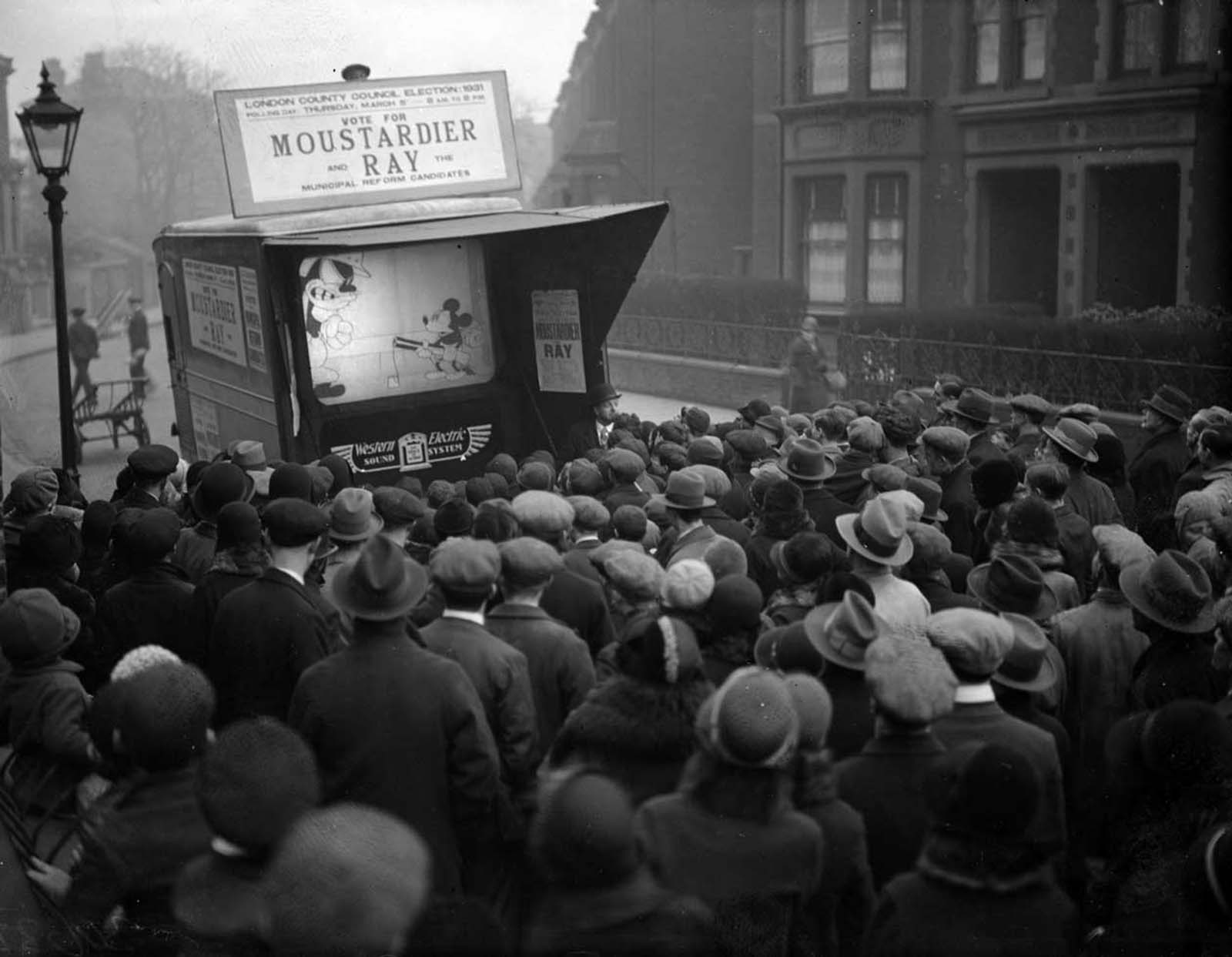 During a London County Council election campaign run, Mickey Mouse is showing on a small screen in a city street. 1931.