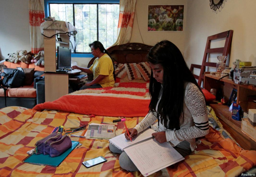 Claudia Bustillos, de 17 años, toma clases en línea en casa mientras su madre María Elena trabaja en una computadora en medio del brote de la enfermedad por coronavirus / REUTERS