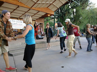 Outdoor music venue with young and old dancing.