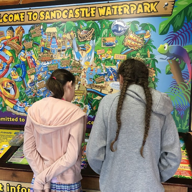 stephs two girls looking at sandcastle waterpark map