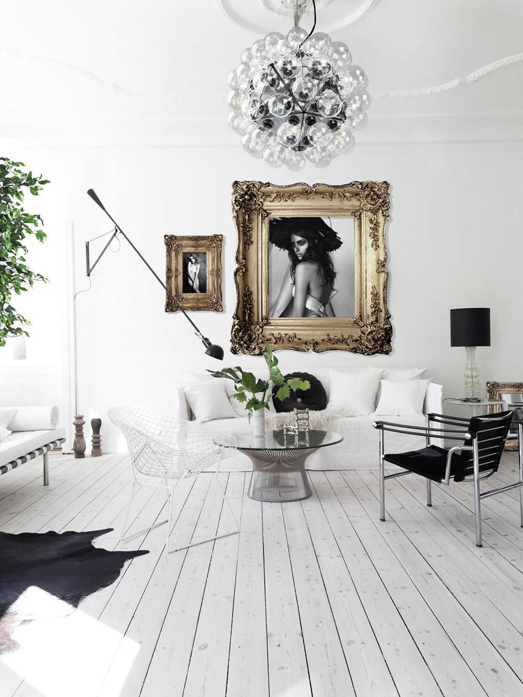 Salón de estilo nórdico con enormes fotografías en marcos dorados y lámpara Taraxacum de Flos