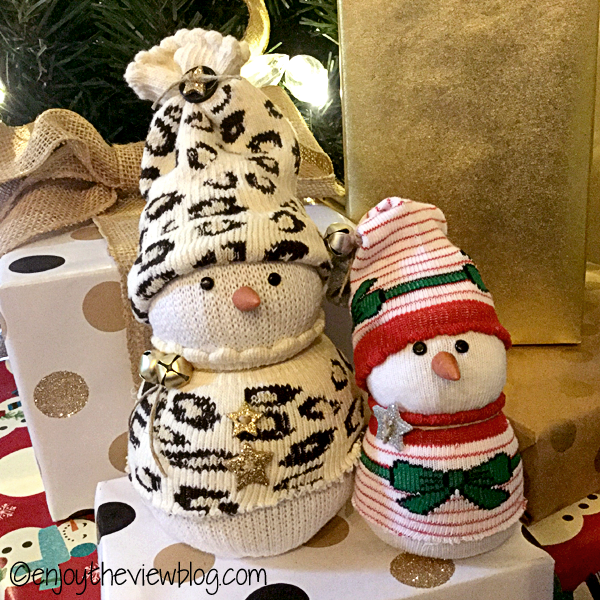 sock snowmen sitting under a Christmas tree