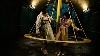 Two people on a fairground swing in a tunnel