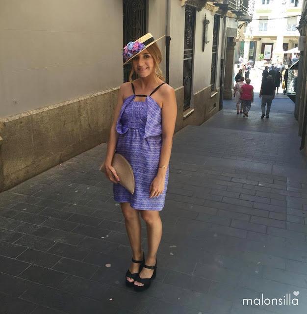 Look invitada boda con vestido corto en azul y malva, canotier de flores de copa baja y bolso abanico