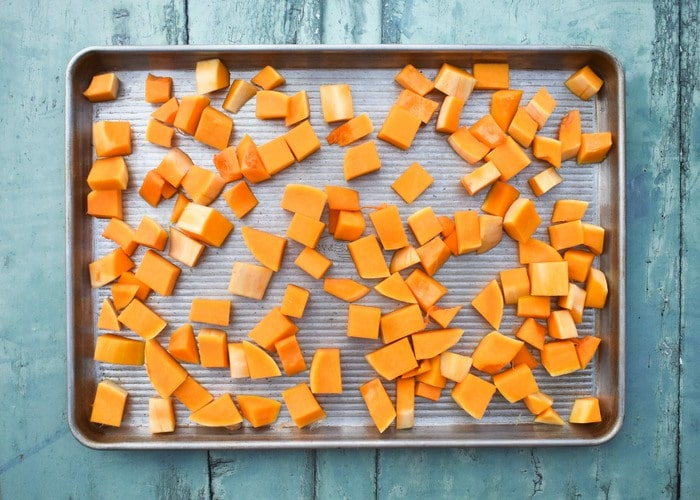 chopped butternut squash spread out on a baking tray