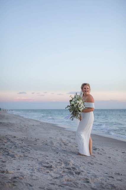 Bride walking down tropical outdoor setting with floral bouquet.