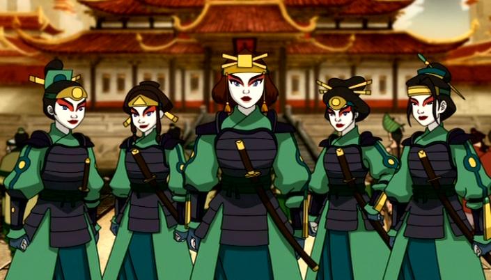 Imagem: as Guerreiras Kyoshi da animação A Lenda de Aang, um grupo de garotas em vestidos verdes com detalhes verde-escuros, por cima um tipo de armadura em tom verde-musgo, luvas, espadas curvas nos cintos, os rostos pintados com uma pintura tradicional asiática, toda em branco e as sobrancelhas com uma pintura avermelhada e em preto, como um arco. Os cabelos pretos e presos em um coque alto e todas carregam leques nas mãos. Ao fundo temos um vale e casas em estilo de estrutura chinesa, com telhados de águas altas e baixas.