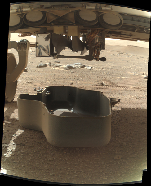 As seen from a camera on Perseverance's robotic arm, the debris shield protecting the Ingenuity Mars Helicopter is released from the belly of the rover...on March 21, 2021.
