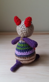 The crocheted joey is facing away from the camera. One can see the red ears, the back of her beige head, her purple arms and stumpy purple tail against the stripes on her body. Her upper body has blue and green stripes, the lower body has beige and brown stripes. Stripe patterns are separated with mauve.