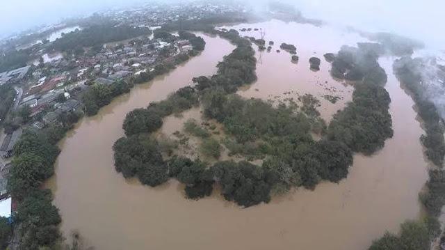 A foto mostra as curvas do Rio dos Sinos transbordando é enchente perigosa.