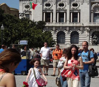 várias pessoas passeando com cravos vermelhos nas mãos