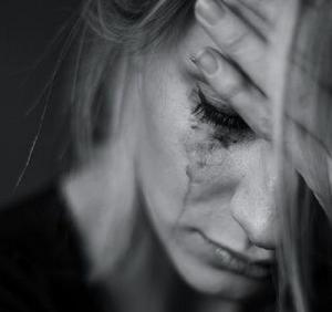 Mujer con la mano puesta en la frente y los ojos casi cerrados, llorando.