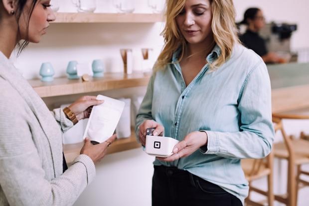 Mulher com a maquininha de cartão frente à sua cliente