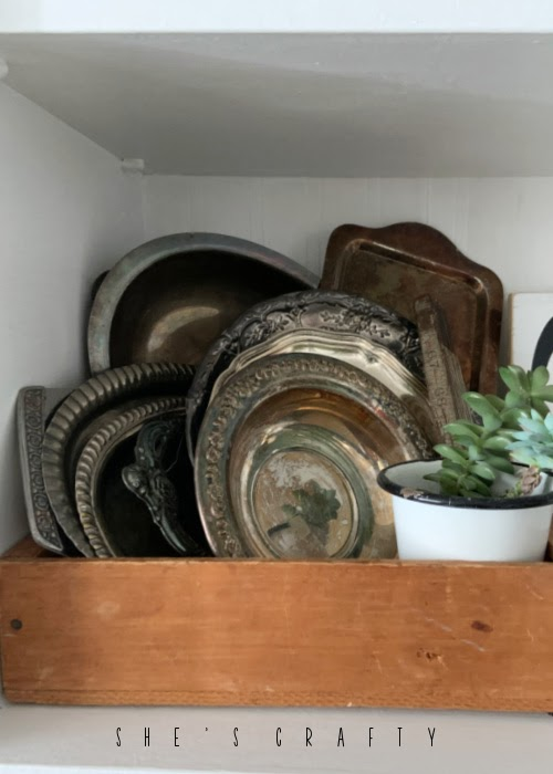 Vintage Silver trays displayed in a wooden crate in a cupboard.