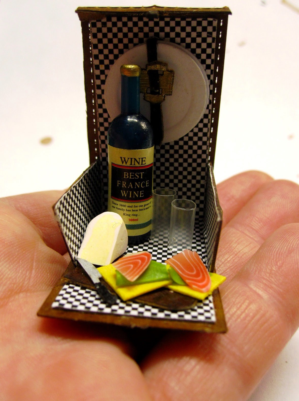 A miniature picnic hamper with black and white checked lining, holding a bottle of wine, two glasses, two smoked salmon sandwiches and a wedge of camenbert, displayed on an outstretched hand.