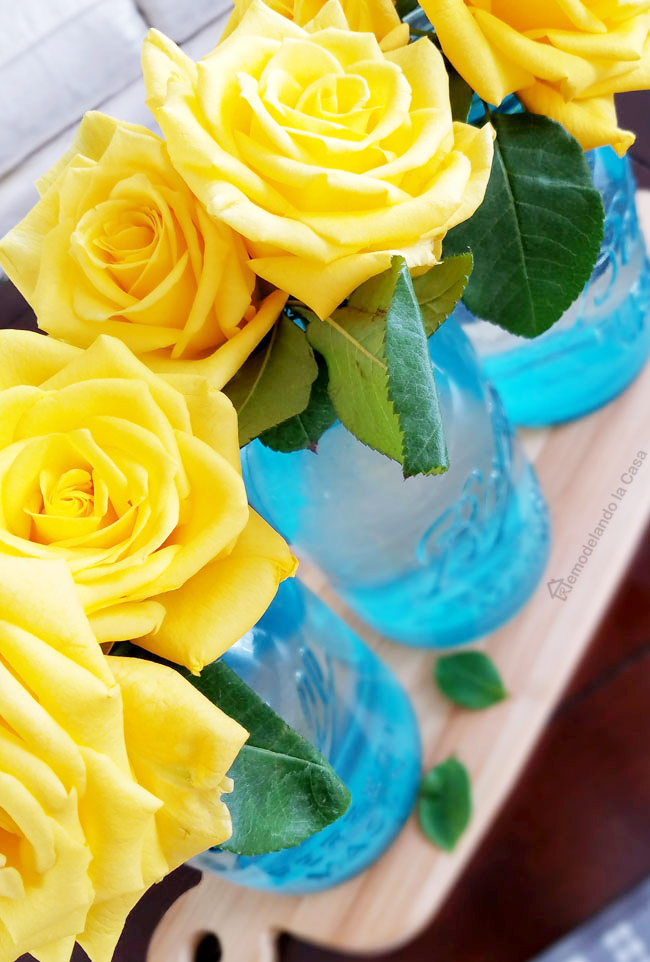 spring decor with yellow roses in blue mason jars