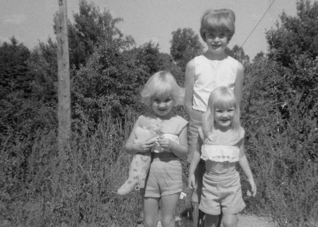 older girl with two younger girls, all in summer shorts and tops.