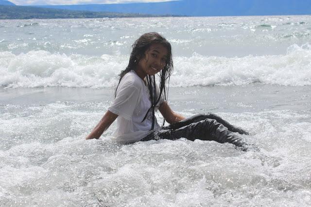 Aku merasa bahagia dapat menikmati segarnya air Danau Toba dengan ombak putihnya