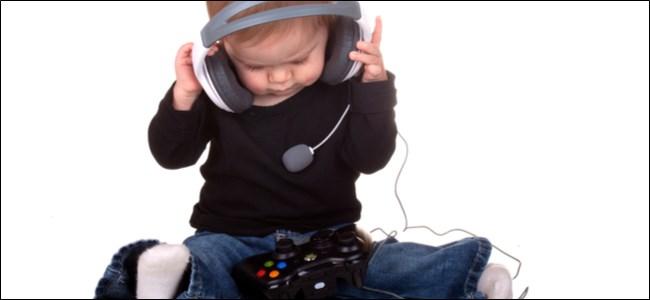 طفل صغير يرتدي سماعة رأس مع وحدة تحكم Xbox في حضنه.