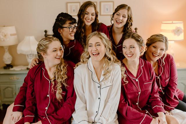 laughing bride and bridesmaids in burgundy pajamas